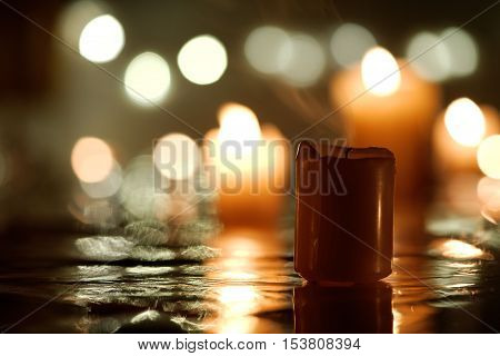 Extinct candle with reflection against defocused candlelight background