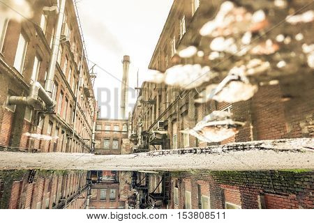 Puddle reflection of abandoned factory in Saint Petersburg neighborhood in Russia - Urban decay concept with forgotten places around the world - Soft focus due to water reflection - Retro desat filter