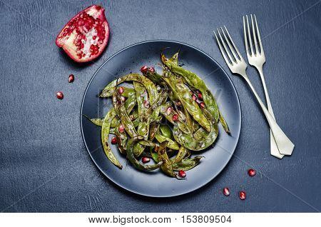roasted snap green beans with Pomegranate on a black background