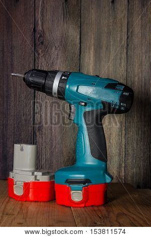 Cordless drill with battery on a wooden background warm shade.