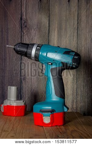 Drill on wooden background with the spare battery.