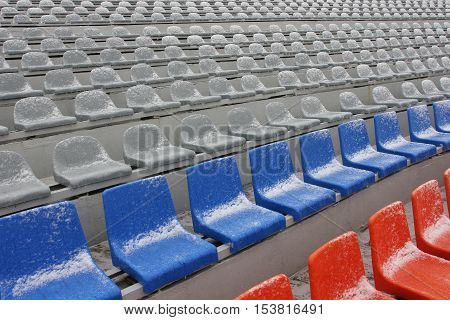 Colored Empty Stadium Seats in snow,  blue, grey, red