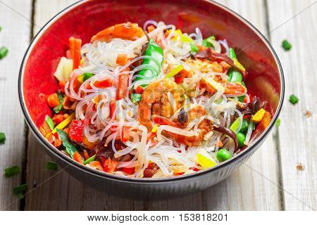 Vegetables with noodles and shrimp on old wooden table