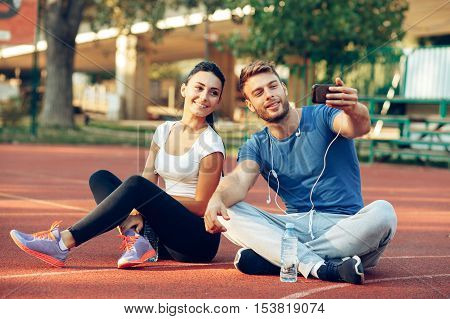 Young couple doing selfie after running outdoors