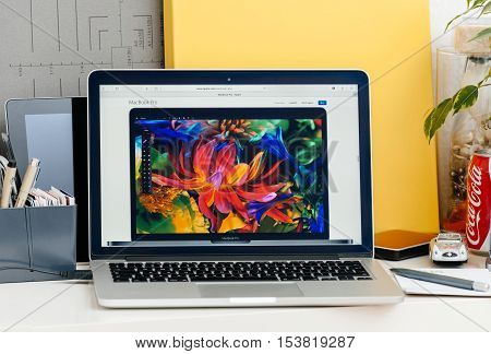 PARIS FRANCE - OCT 28 2016: Apple Computers website on new MacBook Pro Retina with OLED touch bar in a geek creative room showcasing new professional laptop - front view of the new screen with wide gamut