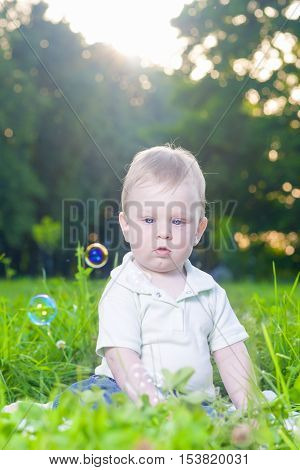 Portrait of Little Cute Caucasian Boy Sitting Alone on Grass Outdoors. Vertical Image
