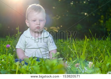 Portrait of Little Cute Caucasian Toddler Child Sitting on Grass Outdoors. Horizontal Image