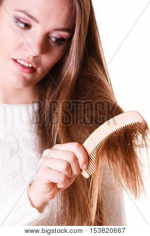 Dissatisfied woman combing with brush and pulls at her long hair. Being unhappy for nice look in daily activity.