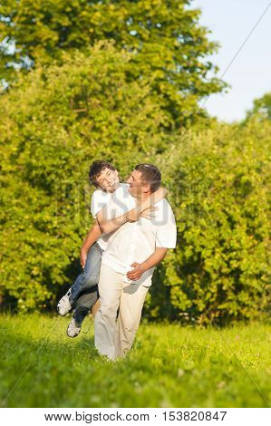 Family Values. Happy Caucasian Family of Father and Son Piggybacking Outdoors. Against Nature Green Forest. Vertical Image Orientation