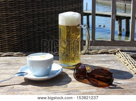 Beer and coffee at the table on the terrace. Drinks near the lake. Beer and coffee with sunglasses on the sunny table.