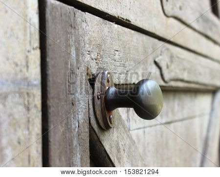Vintage bronze door handle on the wooden door. Closed door with door handle detail. Rustic crafted door.