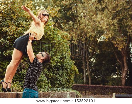 Love romance fun outdoor concept. Girl falling caught by boyfriend. Young lady held by her man in air. poster