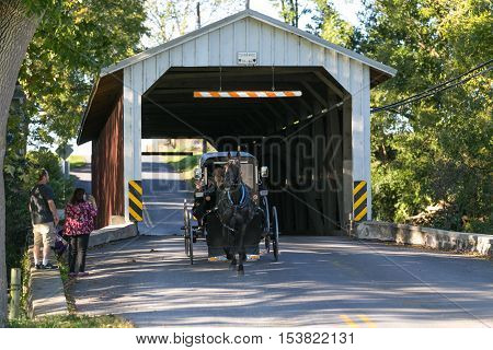 Paradise PA - October 9 2016: Tourists snap a picture of an Amish buggy as it exits a covered bridge in Lancaster County.