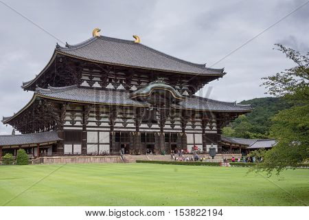 Nara Japan - September 21 2016: Side view of the tall wooden Todai-ji temple building which holds the largest statue of Buddha called Daibatsu in Japan. People in front green lawn gray sky.