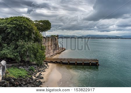 View from Castillo San Felipe del Morro to the harbor. Wooden dock. Angry stormy sky in San Juan Puerto Rico