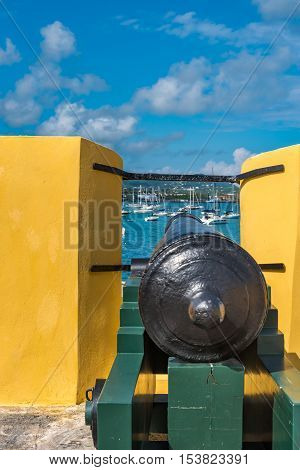Vintage cannon through the turret facing the sailboats in the Caribbean
