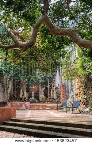 Statue in public courtyard with benches. Brick walls in disrepair. Grungy and in ruins. Covered by large shade trees.