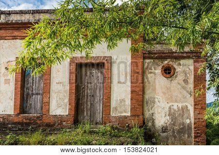 Brick and concrete structure along the road with old wooden doors abandoned and in disrepair.