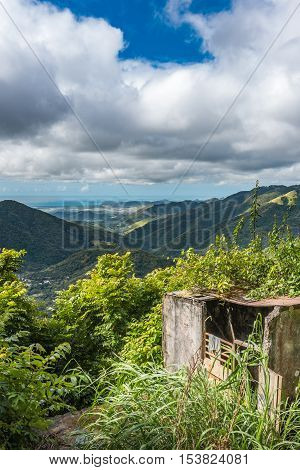 Old concrete structure with beautiful Puerto Rican valley in the background. Cloudy sky and breakthrough sun on the foreground.