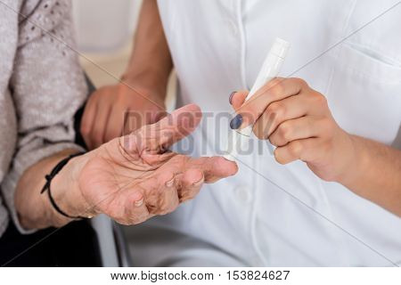 Close-up Of Doctor Holding Patient's Finger Checking Sugar Level With Glucometer