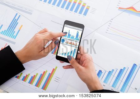 Close-up Of Businesswoman Analyzing Financial Graphs Using Smartphone On Desk