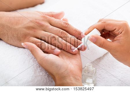 Close-up Of A Manicurist Applying Moisturizing Nail Oil On Person's Hand