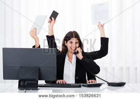 Busy Businesswoman Multitasking At Desk In Office