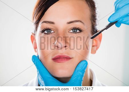 Close-up Of A Surgeon's Hand With Scalpel Near Young Woman's Face