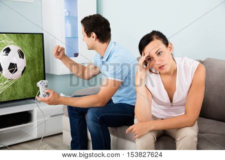 Frustrated Woman Sitting Beside A Busy Man Addicted To Videogame At Home