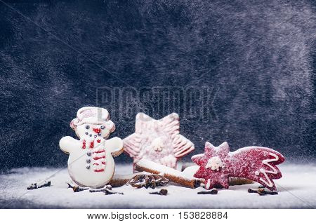 Christmas decoration and cookies. Storm and windy. Flour and spices for a christmas baking on a dark background. Snowman, stars, cinnamon, comet.