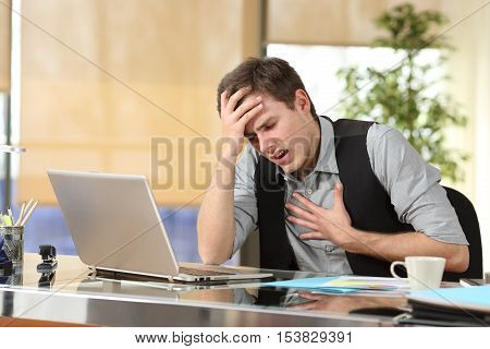 Businessman suffering an anxiety attack with the hands in his chest and head sitting in a desktop at office