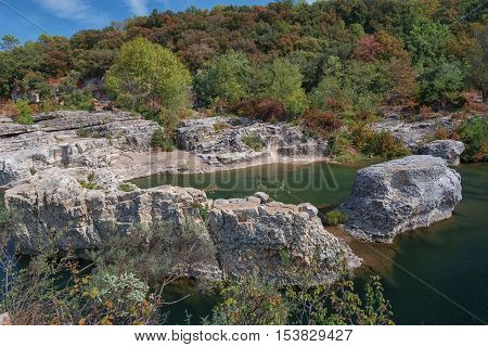 At the foot of the hill on which La Roque sur Cèze in France lies swirl spectacular waterfalls and rapids of the Cascades du Sautadet.