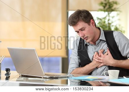 Businessman suffering a heart attack with his hands grabbing the chest sitting in a desktop at office