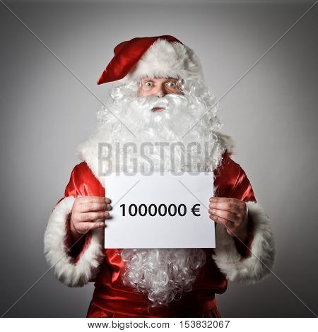 Santa Claus is holding a white paper in his hands. One million Euro concept.