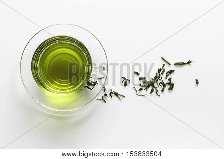 transparent glass cup with green tea on the saucer with dry tea leaves on a white background