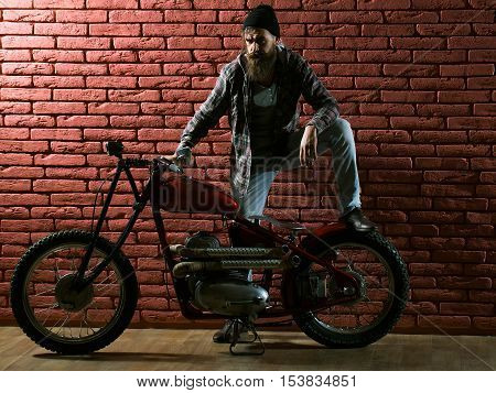 young handsome bearded man hipster or biker with long beard near metallized motorbike or motor cycle with wheels on red brick wall background in garage