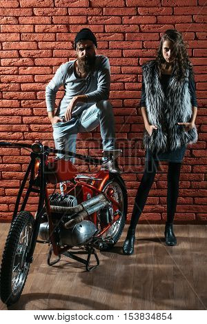 pretty sexy cute woman or girl with young handsome bearded man hipster or biker with long beard near metallized motorbike or motor cycle with wheels on red brick wall background in garage