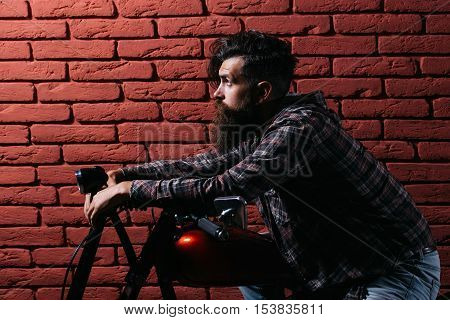 young handsome bearded man hipster or biker with long beard sitting on metallized motorbike or motor cycle on red brick wall background in garage