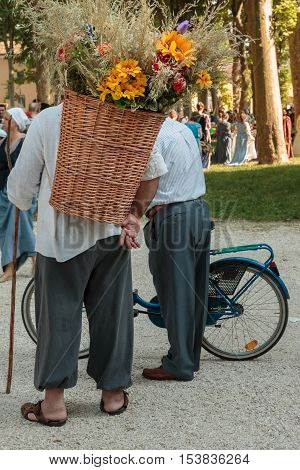 Wicker Basket Filled with Sheafs of wheat and Flowers Carried over the Shoulder of Countryman and Old Man with Bicycle