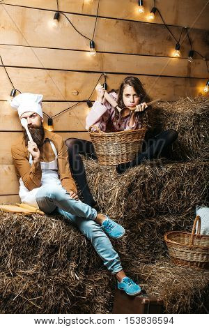 Funny man chef cook or baker with beard and moustache in hat toque and cute girl cookee teenager in apron sit on straw bales on rustic background