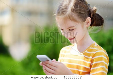 Cute Little Girl Playing Outdoor Mobile Game On Her Smart Phone