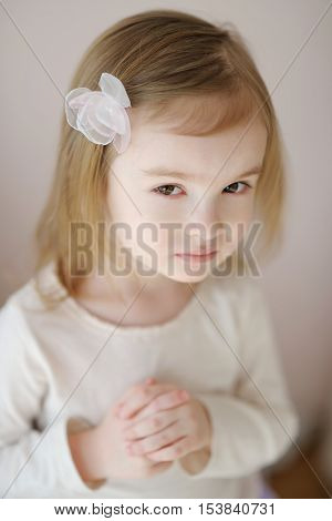Adorable little girl with flower hairclip at home
