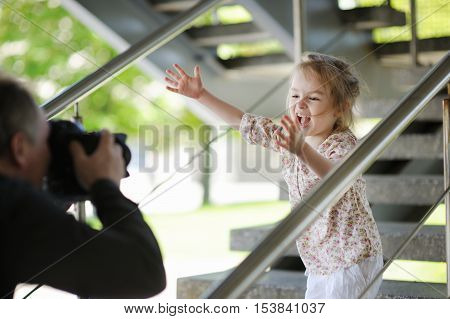 Father Taking Picture Of Smiling Young Girl