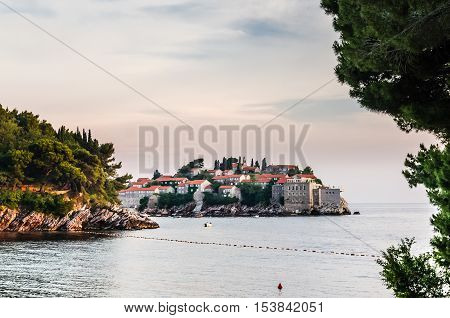 Evening view on Sveti Stefan island from Milocer beach in Montenegro. Toned photo