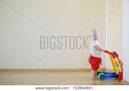 Cute Smiling Baby Girl With Toy Walker