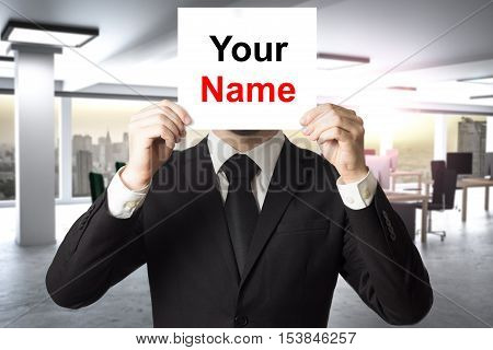 businessman in office hiding face behind sign your name