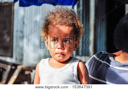 MANA ISLAND, FIJI - AUGUST 20, 2012: Kid with frightened look in a local village in Mana Island Fiji