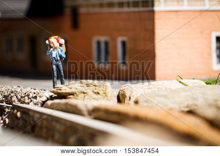 Small hiker figure walking with backback in city.