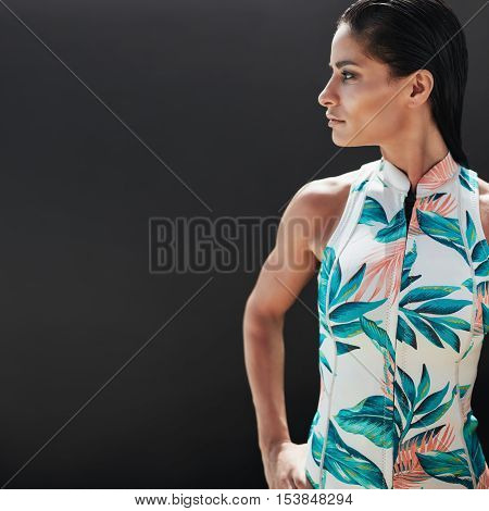 Portrait of beautiful young woman standing against black background and looking away at copy space. Attractive female model posing in a casual sleeveless top.