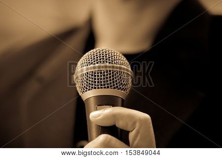 blurred of businessman speech talking public speaking with microphone